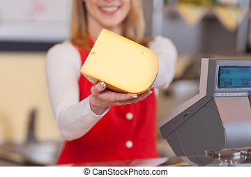Saleswoman showing cheese chunk - Close-up of a saleswoman ...
