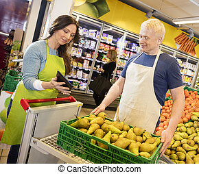 Saleswoman Showing Digital Tablet To Colleague In Fruits Departm