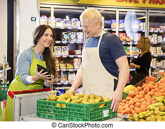Saleswoman Showing Digital Tablet To Colleague Working In Fruits