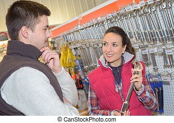 saleswoman showing tool to male customer in hardware store