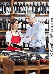 Saleswoman Showing Wine Bottle To Male Customer