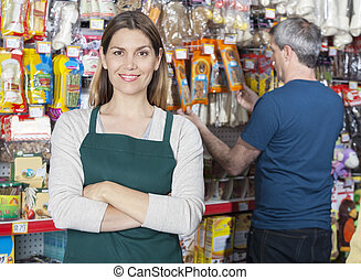 Saleswoman Standing Arms Crossed While Customer Selecting...