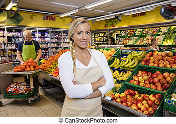 Saleswoman With Arms Crossed Standing By Fruit Crates