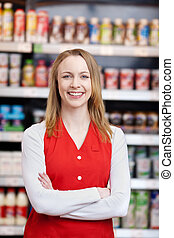 Saleswoman With Arms Crossed Standing In Grocery Store - ...