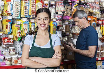 Saleswoman With Arms Crossed Standing While Customer Selecting P