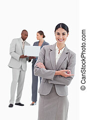 Saleswoman with talking colleagues behind her