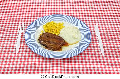 Salisbury steak gravy dinner on red checkerboard cloth