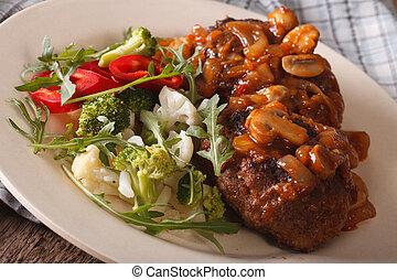 Salisbury steak with mushroom sauce and vegetables close-up....