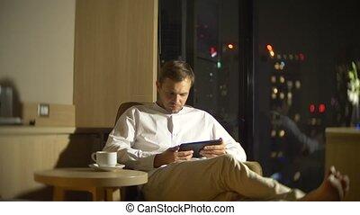 salle, négligence, panoramique, ordinateur portable, jeune, arrière-plan., fenêtre, homme, barbouillage, utilisation, chaise, beau, night., gratte-ciel