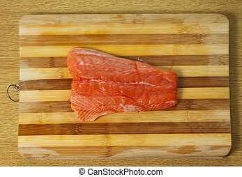 Salmon - A piece of salmon over a wooden chopping board