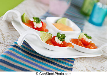 salmon bouche - salmon served on a bouche spoon on a plate