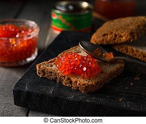 Salmon caviar on rye bread on dark wooden rustic background