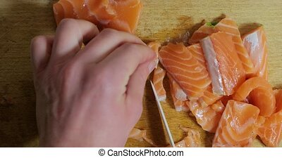 Chopping salmon fillet on a cutting board, fresh red fish pieces