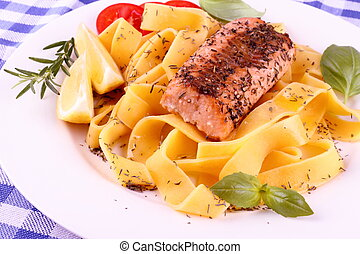 Salmon fillet on tagliatelle, lemon and herbs, close up