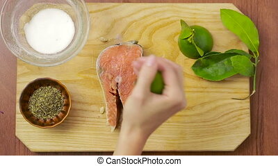salmon fillet with lemon lime dill and spices. top view. woman preparing fish