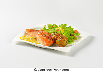pan seared salmon fillet served with roasted potatoes and fresh vegetables