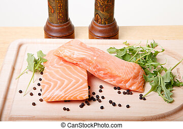 Salmon Fillets on Board with Peppercorns and Arugula