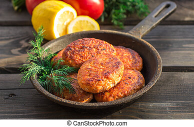 salmon fishcakes in a cast iron skillet, tomatoes and lemon ...