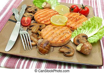 Salmon medallion, stuffed snails and mushrooms on a plate