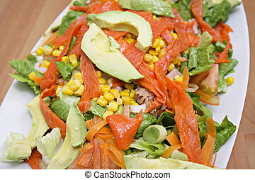 salmon salad with sweet corn and vegetables on white dish