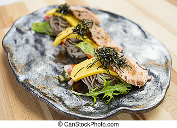 Salmon Soba with noodle, herbs and seaweed on black platter