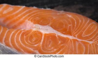 Salmon steak fried in a pan. Slow motion 100f