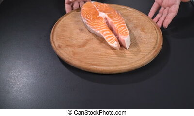 Salmon steak on a cutting board. Slow motion - Cook shows...