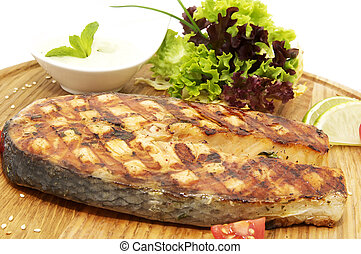 salmon steak cooking on the grill with fresh herbs and sauce