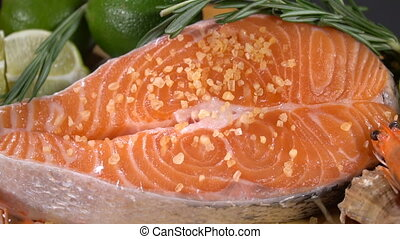 Salmon steak sprinkled with spices. Slow motion - Raw salmon...