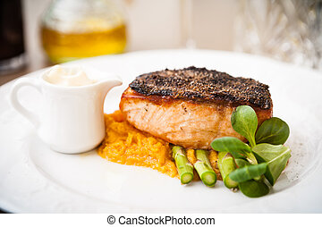 Salmon steak with asparagus and sweet potato mash served on...