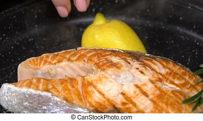 Salmon steak with lemon in a pan. Slow motion - Grilled...