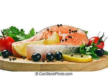 salmon steak with slices of lemon, black pepper