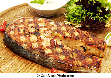 Salmon steak with herbs and lemon on a wooden platter