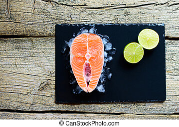 Salmon steaks with lime on ice on black wooden table top view. Fish food concept. Copy space