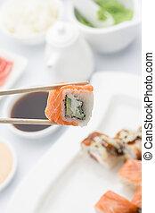 Salmon sushi roll in chopsticks