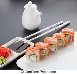 Salmon sushi roll on a white plate with ginger wasabi chopsticks and sauces over black background