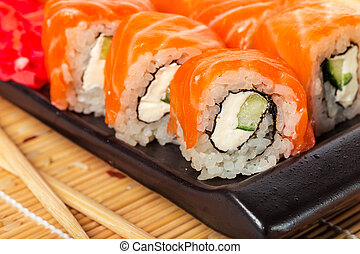 Salmon sushi rolls on a wooden background