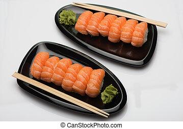 Salmon sushi, wooden sticks and wasabi on two black ceramic...