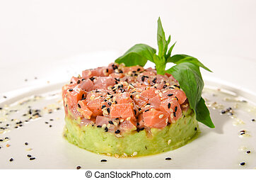 Salmon tartar serve with sesame seeds on a bed of vegetables