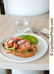 Salmon toast with avocado and vegs in the modern cafe