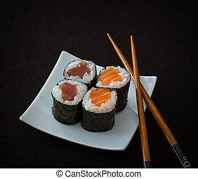 Salmon, tuna maki sushi and chopstick on black, top view