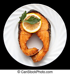Salmon with lemon on a plate on a black background