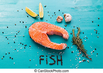 Salmon with lemon, pepper and rosemary on blue background top view and the inscription pepper fish. Keto diet, pescetarianism and healthy food concept.