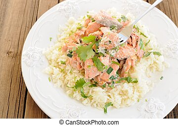 Salmon with rice, scallion and cilantro in white plate with fork on wooden background top view horizontal