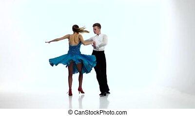 Salsa dancing couple of professional elegant dancers,slow motion. White studio