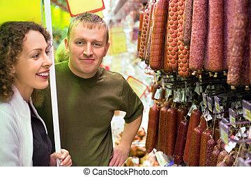 salsiccia, donna, giovane, supermercato, comprare, uomo sorridente