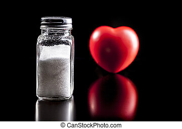 Salt And Heart - Salt and heart isolated on black background...