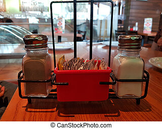 salt and pepper container on a table in a restaurant
