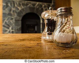 Salt and Pepper in glass on the wooden