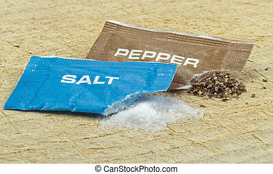 Salt and pepper sachets - Open salt and pepper sachets on a...